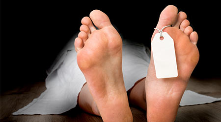 Dead woman lying on the floor under white cloth with blank tag on feet