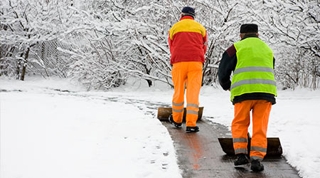 Workers removing first snow from pavement