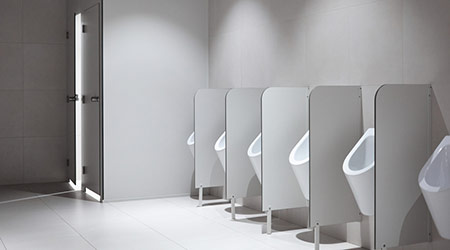 Row of clean porcelain sensor-operated male urinals with partitions