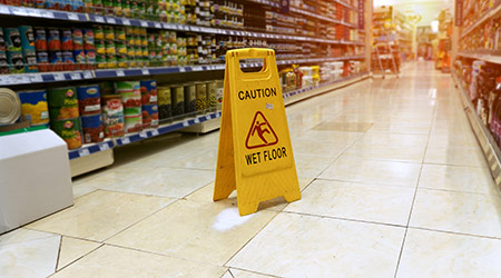 Wet floor sign in grocery store aisle