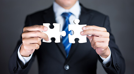 Businessman hold connecting puzzle pieces representing the merging of two companies or joint venture, partnership