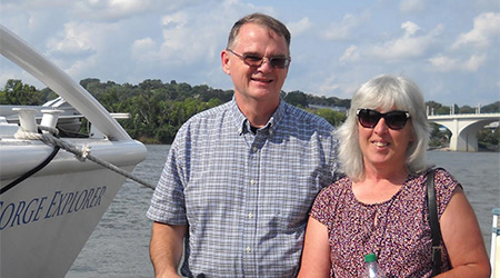 older man in sunglasses standing next to an older woman and a boat