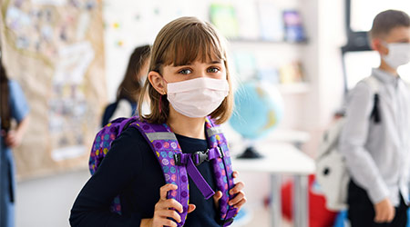 Child with face mask going back to school after covid-19 quarantine and lockdown