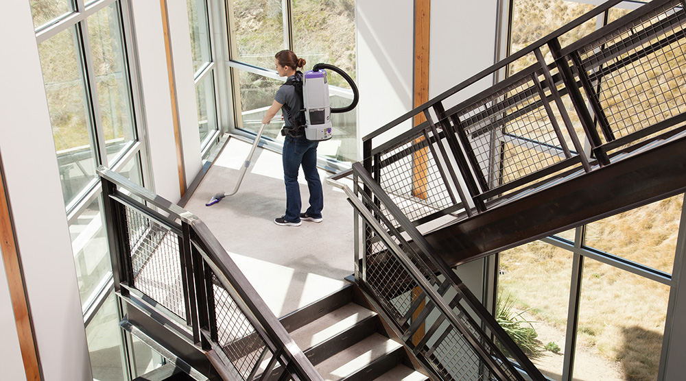 Person using vacuum on staircase with windows.