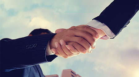 Worm eye view shot of businessmen handshaking.acquisition concept.