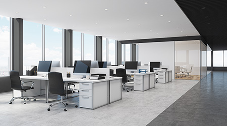 Side view of open space office interior with rows of computer tables with desktops standing on them.
